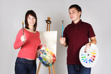 young man and girl standing near easel, holding brushes with pal poster