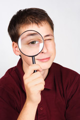 young man holding magnifier and looking through it, big eye