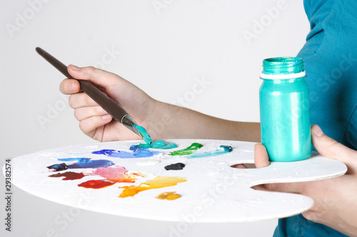 closeup of woman in blue shirt mixing paint on palette