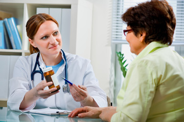 A doctor prescribes a medicine to a senior patient
