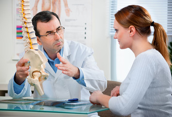 Doctor shows the problem areas on the spine's model to patient