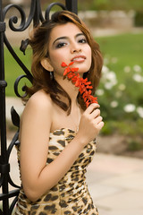 Exotic brunette leaning against iron gate holding flower
