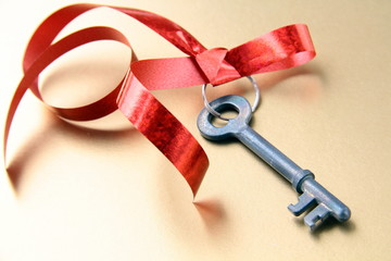 old key with a red ribbon  on  gold  background