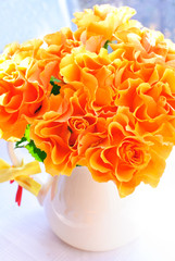 Orange roses in milk jug