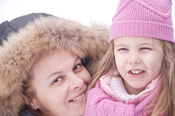 Happy mom and girl in snow