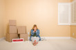 Upset Woman on Floor Next to Boxes and Foreclosure Sign