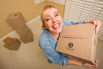 Excited Woman Holding Moving Boxes in Empty Room