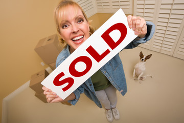 Woman and Doggy with Sold Sign Near Moving Boxes