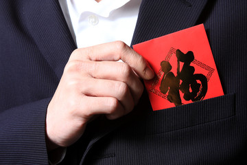 businessman putting chinese cash gift in his pocket