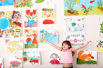 Child in art class with picture.