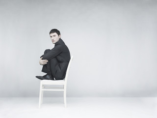 Man sitting on a white stool