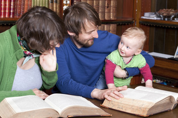 Happy family with a baby in classic library