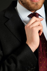 Detail of a young businessman correcting a tie