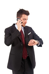 Businessman talking at the phone and looking at his watch