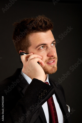 Confident businessman talking at the phone on black background