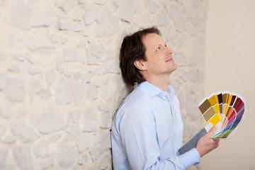 mann mit farbfächer plant den innenausbau
