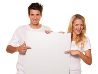 Paar mit leerem Poster zur Werbung für Eröffnung