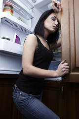 beautiful brunette on background of an open refrigerator