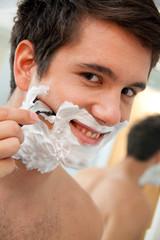 Mann rasiert sich mit Rasierklinge Und Rasierschau