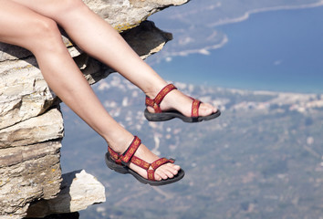 Woman with trekking sandals sitting on rock high above the sea