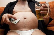 Nadwaga człowiek siedział na kanapie ze szklanką piwa