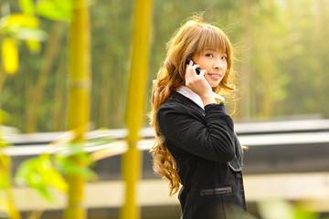 businesswoman talk phone beside trees