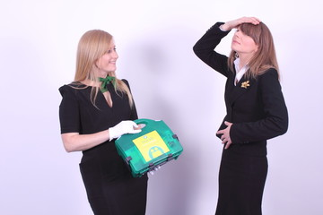 office: woman in pain and woman with first aid kit