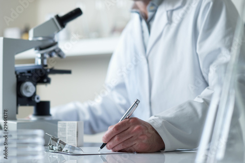 scientist conducting research with microscope - 29444378