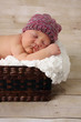 Newborn baby girl asleep in a basket.