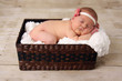 Baby girl asleep in a basket.