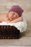 Newborn baby girl asleep in a basket.
