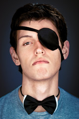 arrogant young  man in the piratical eye-band and bow tie