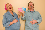 Pregnant Laughing Couple Deciding on Pink of Blue Wall Paint. poster