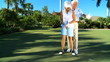 Retired Gentleman Teaching his Wife to Play Golf