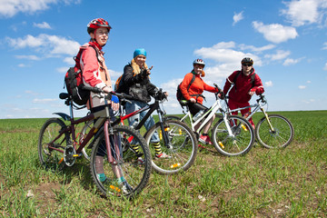 A group of four adults on bicycles in the countryside.