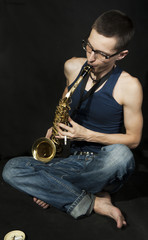 close-up  cross-legged young jazzman plays a saxophone