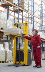 Senior worker in red uniform with bar code reader in warehouse