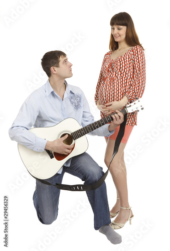 Pregnant woman and a man playing guitar for her