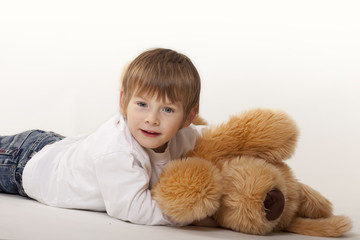 boy lying on teddy bear