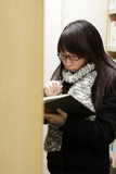 An Asian girl who is reading book in library