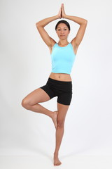 Beautiful young woman in tree pose during yoga