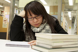 An Asian girl who is reading and studying in library