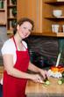 freundliche hausfrau beim kochen