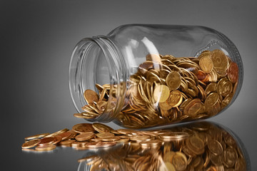 coins spilling from a money jar on gray background