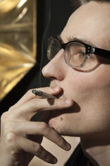 pensive young man in glasses smoking a cigarette