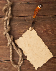 Old paper pinned to a wooden wall with a knife