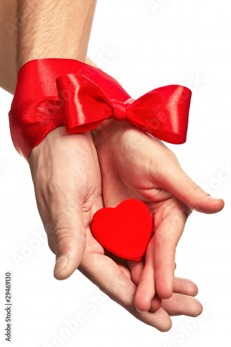 hands are binding by crimson ribbon with small scarlet heart