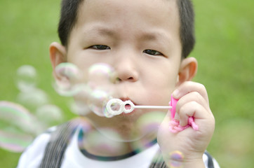 asian kid blowing soap bubble