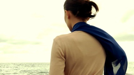 Young woman thoughtfully looking out to sea