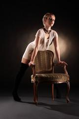Frau im weissen Kleid steht sexy hinter einem Lehnstuhl